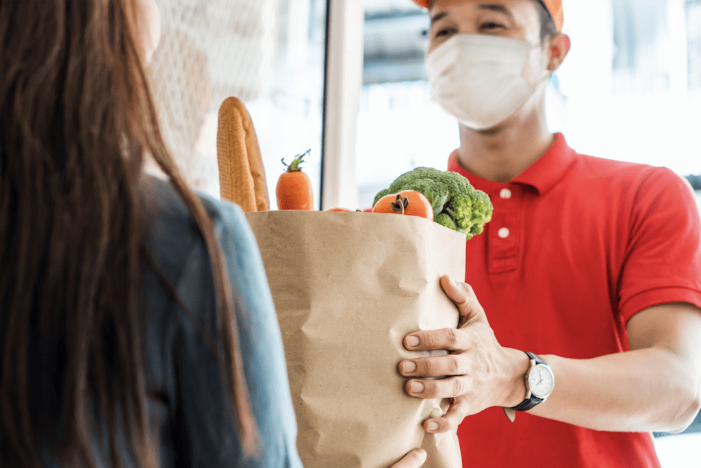 A man delivers a food box to a woman experiencing food insecurity.
