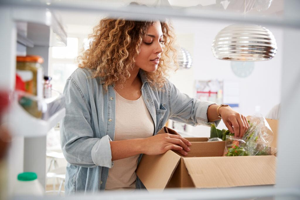 A woman experiencing food insecurity opens a food delivery box.